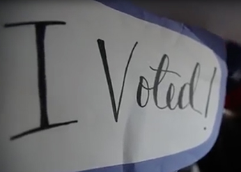 A voting sign is held by a student in Northwestern's Voter Van.