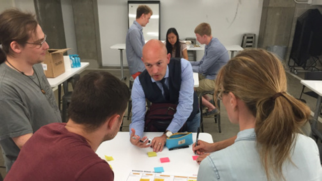 Marc McLaughlin, partner at Business Models, Inc., gives feedback to students Sofya Akhmametyeva (right), Austin Speelman (middle) and Nathan Corwin, who run the startup AIR, during summer Wildfire 2016 at The Garage