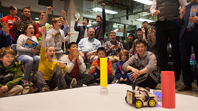 A group of people cheer while looking at a small robot vehicle on the floor.