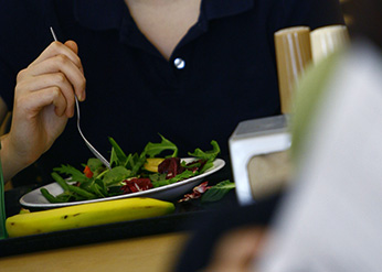 A hand holds a fork touching a salad on a plate.