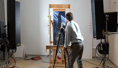 Researcher in front of painting with camera